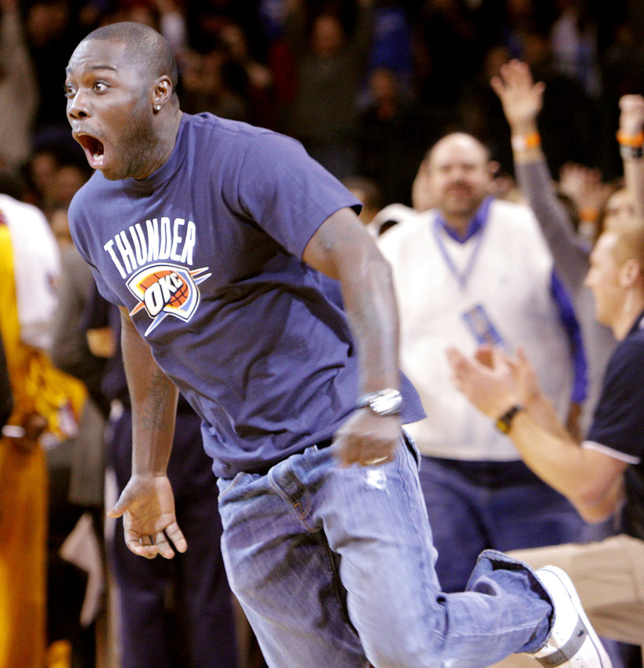 Photo - An Oklahoma City fan reacts after hitting a $20,000 half-court shot during a break in the  NBA basketball game between Oklahoma City and Cleveland at the OKC Arena in Oklahoma City on Sunday, Dec. 12, 2010. Photo by John Clanton, The Oklahoman