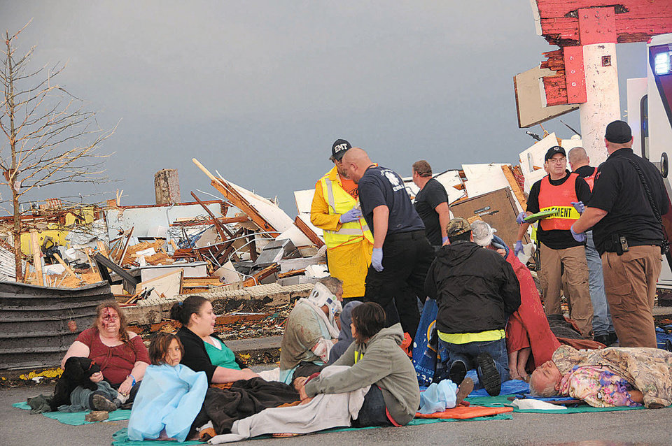 Photo - A triage team treats wounded people at a triage station set up at Twenty-sixth and Main Streets in Joplin, Mo. after a tornado swept through the city on Sunday evening, May 22, 2011.  (AP Photo/The Joplin Globe, Mari Taylor) ORG XMIT: MOJOP102