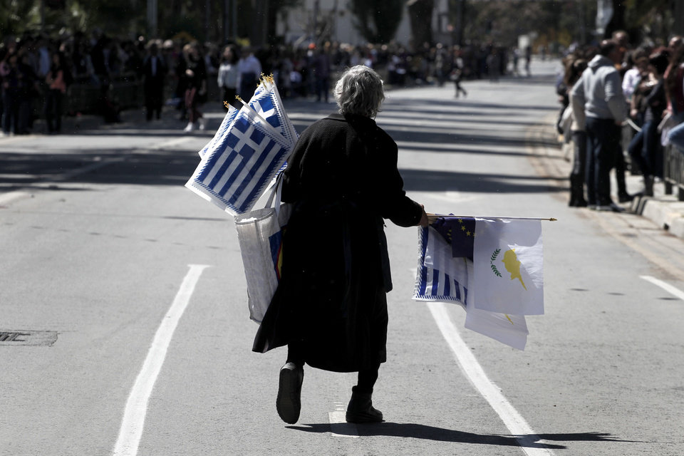 """Photo - An elderly woman sells Greek, Cypriot, and EU flags before the start of a parade for Greek Independence Day celebrations in capital Nicosia, Cyprus, Monday, March 25, 2013. Cyprus secured what its politicians described as a """"painful"""" solution to avert imminent bankruptcy, agreeing early Monday to slash its oversize banking sector and make large account holders take losses to help pay to secure a last-minute euro10 billion (US$13 billion) bailout. (AP Photo/Petros Giannakouris)"""