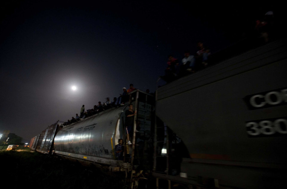 Photo - In this July 11, 2014 photo, Central American migrants wait on a stopped freight train during their journey toward the U.S.-Mexico border after reports that robbers had boarded the train and where stealing from the migrants, in Chahuites, Mexico. The police stopped and checked the train and eventually let it go as nothing out of the ordinary was found. (AP Photo/Eduardo Verdugo)