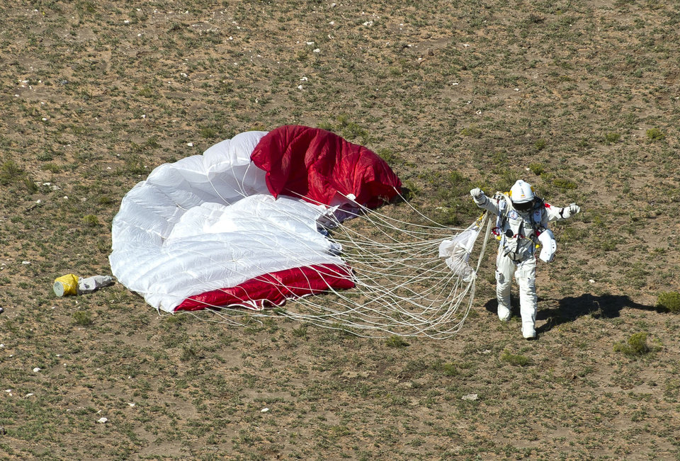 In this photo provided by Red Bull, pilot Felix Baumgartner of Austria celebrates after his successful jump on Sunday, Oct. 14, 2012 in Roswell, N.M. Baumgartner came down safely in the eastern New Mexico desert minutes about nine minutes after jumping from his capsule 128,097 feet, or roughly 24 miles, above Earth (AP Photo/Red Bull Stratos, Predrag Vuckovic) MANDATORY CREDIT ORG XMIT: NY208