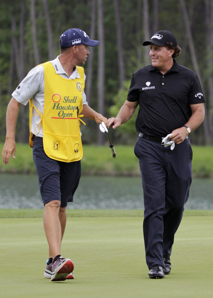 Photo - Phil Mickelson, right, smiles at his caddie Jim Mackay as he birdies on the fourth hole during the first round of the Houston Open golf tournament on Thursday, April 3, 2014, in Humble Texas. (AP Photo/Patric Schneider)