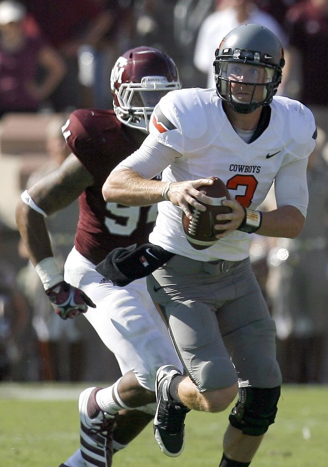 Oklahoma State 's Brandon Weeden scrambles as he is chased by Texas A&M's Damontre Moore (94) in the first half of their game Saturday in College Station, Texas. Photo by Sarah Phipps, The Oklahoman