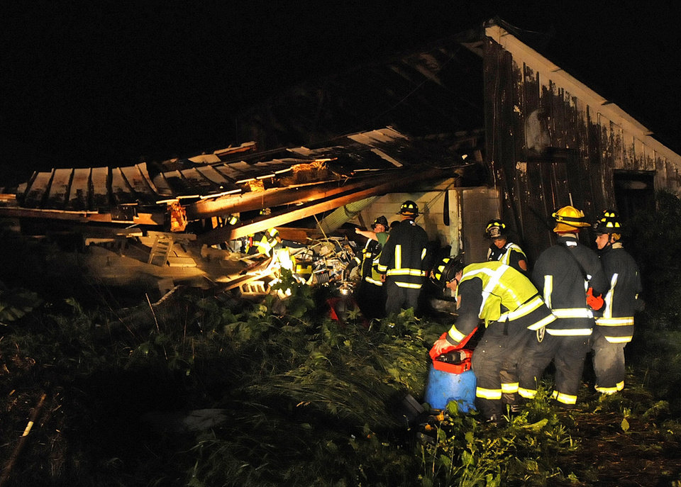 In a Wednesday, June 12, 2013 photo, Manteno, Ill., firefighters enter a barn that collapsed trapping as may as 11 horses as a powerful thunderstorm swept through the area. Thunderstorms that punched through northern Illinois overnight caused significant wind damage, mainly in rural areas west and south of Chicago. (AP Photo/The Daily Journal, Mike Voss)