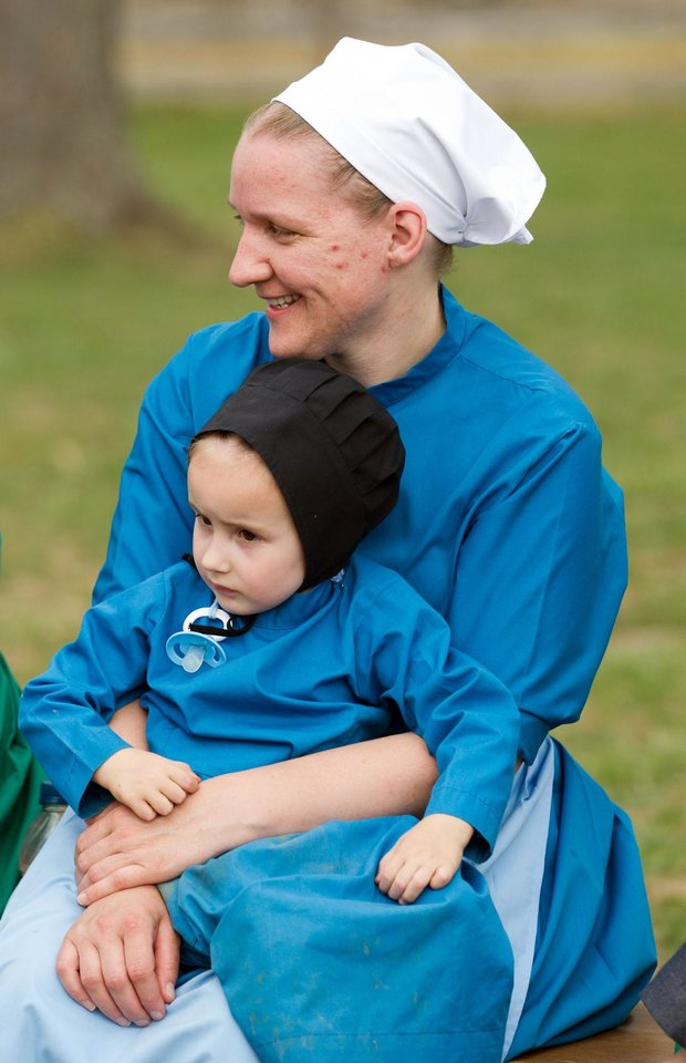 Photo - Anna Miller holds her daughter during a farewell picnic outside the school house in Bergholz, Ohio on Tuesday, April 9, 2013.  The farewell celebration was held for Miller and other Amish members leaving for prison throughout the week for their roles in a hair and beard cutting scandal. (AP Photo/Scott R. Galvin)