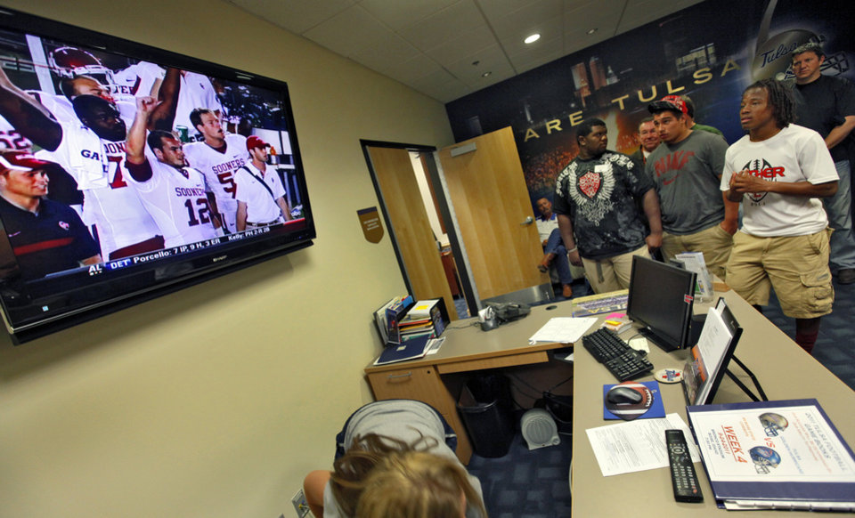 Photo - Football fans watch the University of Oklahoma game on the television during the storm delay of the college football game between the Oklahoma State University Cowboys and the University of Tulsa Golden Hurricane at H.A. Chapman Stadium in Tulsa, Okla., Saturday, Sept. 17, 2011. Photo by Chris Landsberger, The Oklahoman
