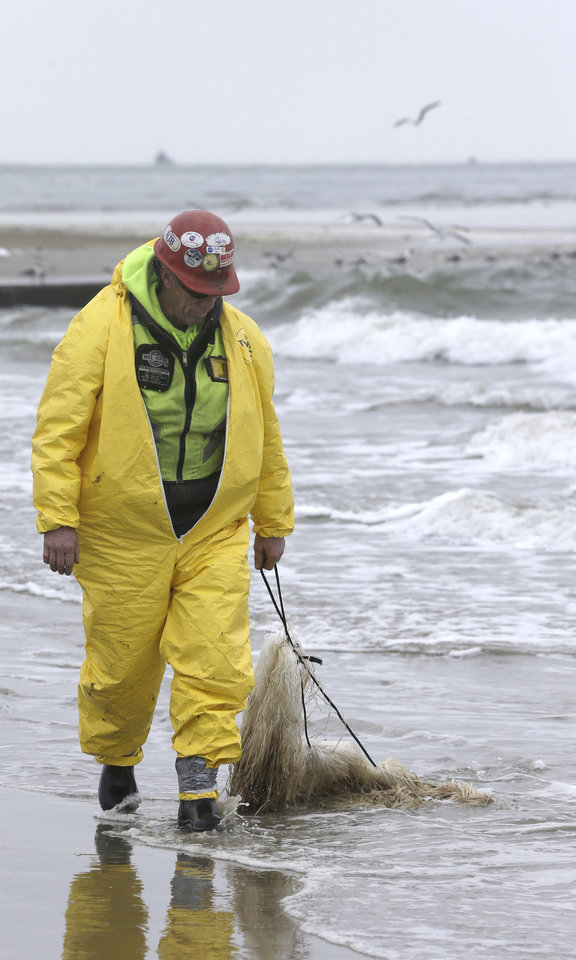 Photo - A worker drags viscous snare pom poms along the waters' edge on East Beach in Galveston, Texas, to snag oil, Monday, March 24, 2014. Thousands of gallons of tar-like oil spilled into the major U.S. shipping channel after a barge ran into a ship Saturday. (AP Photo/Pat Sullivan)