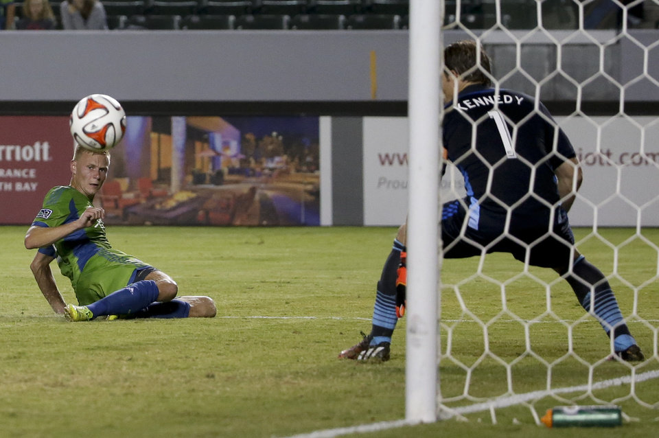 Photo - Seattle Sounders midfielder Andy Rose, left, scores past Chivas USA goalkeeper Dan Kennedy during the first period of an MLS soccer match Wednesday, Sept. 3, 2014, in Carson, Calif. (AP Photo/Chris Carlson)