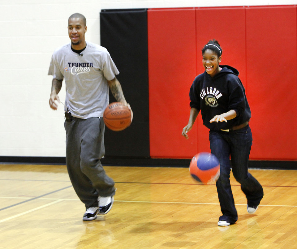 Thunder player Eric Maynor and sixth-grader Tiyuna Gamble practice dribbling during a lesson at Cimarron Middle School in Edmond. PHOTO BY DAVID MCDANIEL, THE OKLAHOMAN <strong>David McDaniel - The Oklahoman</strong>