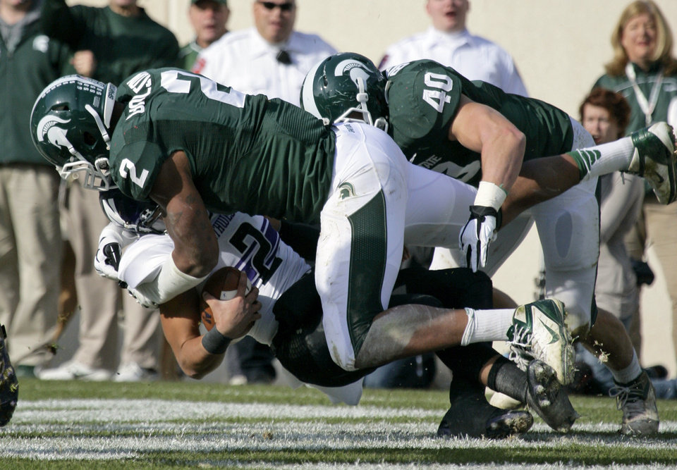 Photo -   Northwestern quarterback Kain Colter, bottom, is sacked in the end zone for a safety by Michigan State's William Gholston with help from Max Bullough (40) during the first quarter of an NCAA college football game, Saturday, Nov. 17, 2012, in East Lansing, Mich. (AP Photo/Al Goldis)