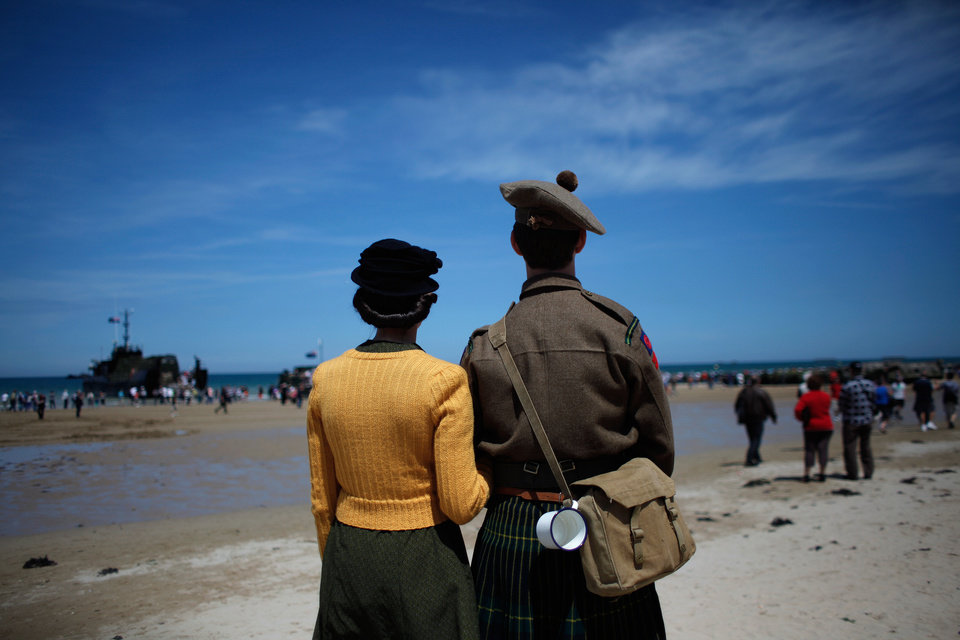 Photo - People wearing WWII style clothes look toward the sea, on the beach of Arromanches, western France , Friday June 6, 2014.  Ceremonies to commemorate the 70th anniversary of D-Day are drawing thousands of visitors to the cemeteries, beaches and stone-walled villages of Normandy this week, including some of the few remaining survivors of the largest sea-borne invasion ever mounted. (AP Photo/Thibault Camus)