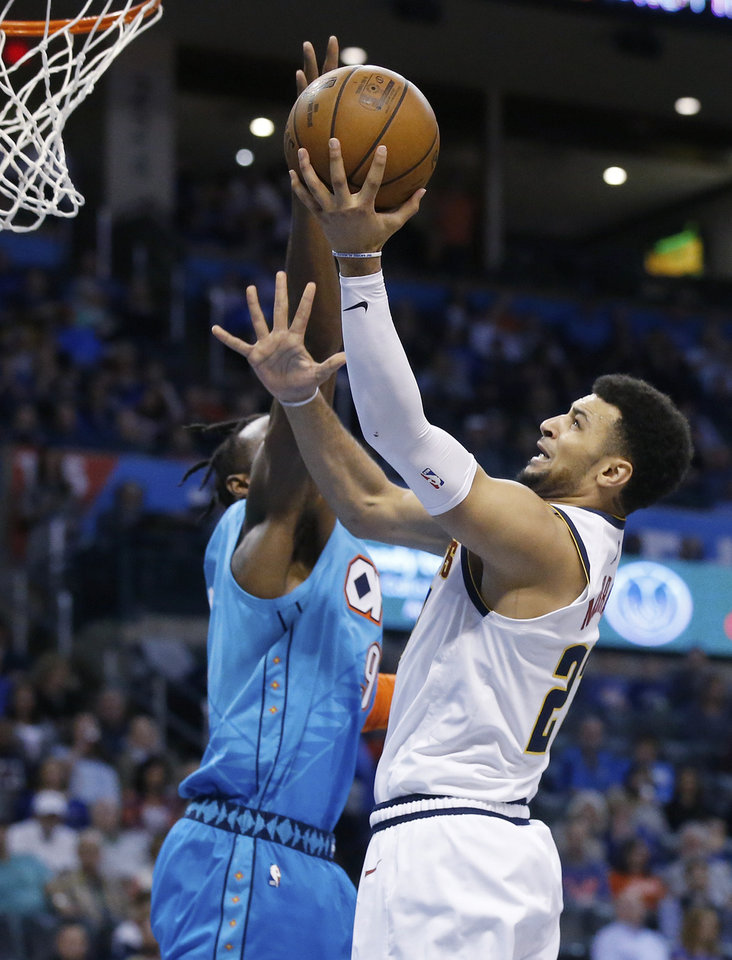Photo - Denver Nuggets guard Jamal Murray, right, shoots as Oklahoma City Thunder forward Jerami Grant, left, defends in the first half of an NBA basketball game Friday, March 29, 2019, in Oklahoma City. (AP Photo/Sue Ogrocki)