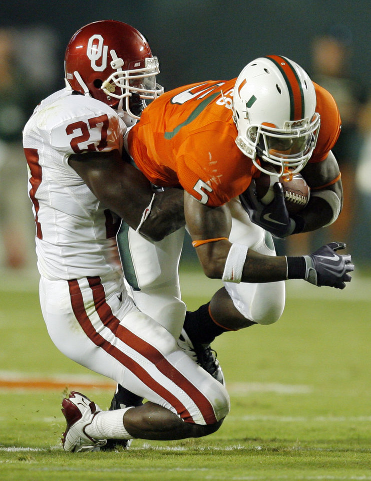 OU's Sam Proctor (27) tackles Miami's Javarris James (5) during the college football game between the University of Oklahoma (OU) Sooners and the University of Miami (UM) Hurricanes at Land Shark Stadium in Miami Gardens, Florida, Saturday, October 3, 2009. Photo by Nate Billings, The Oklahoman