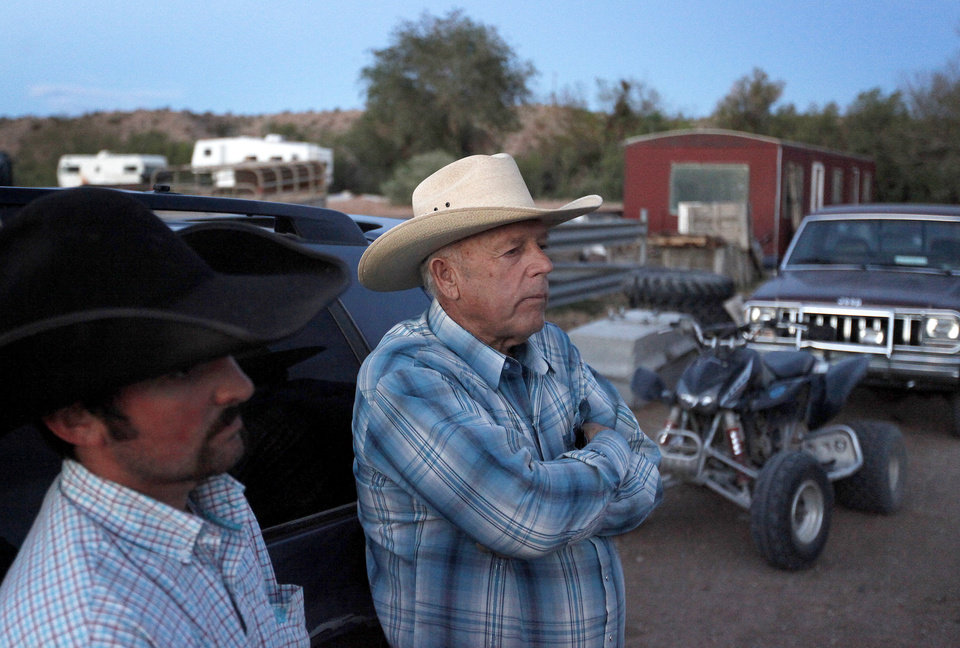 Photo - Cliven Bundy, right, and Clance Cox, left, stand at the Bundy ranch near Bunkerville Nev. Saturday, April 5, 2014. The U.S. Bureau of Land Management started taking cattle on Saturday from rancher Bundy, who it says has been trespassing on U.S. land without required grazing permits for over 25 years. Bundy doesn't recognize federal authority on land he insists belongs to Nevada. (AP Photo/Las Vegas Review-Journal, John Locher)