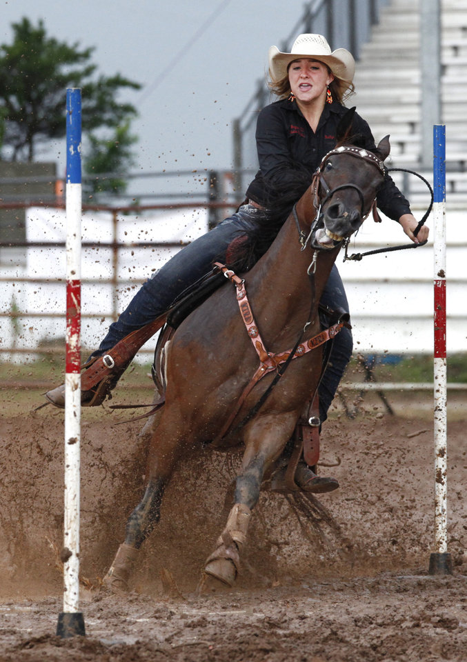 Photo - Marilyn Melvin, Paradise, TX, competes in a muddy Pole Bending at the International Youth Finals Rodeo in Shawnee at the Heart of Oklahoma Exposition Center, Wednesday, July 9, 2014. Photo by David McDaniel, The Oklahoman