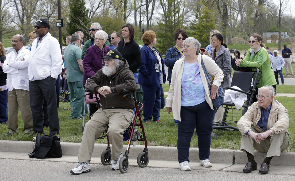 Photo - People wait outside a Veterans Affairs hospital after they were evacuated, Monday, May 5, 2014, in Dayton, Ohio. A city official says a suspect is in police custody after a shooting at the Veterans Affairs hospital in Ohio that left one person with a minor injury. (AP Photo/Al Behrman)