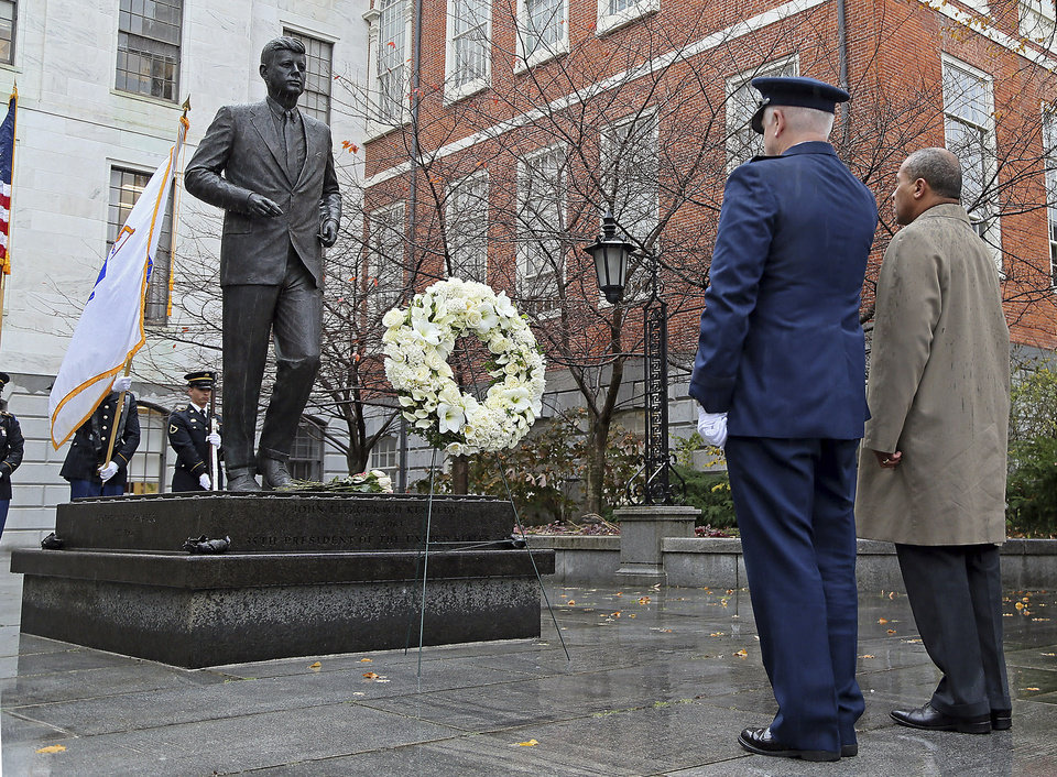 Photo - Gov. Deval Patrick, right, and L. Scott Rice, Adjutant General of the Massachusetts National Guard, lay a wreath at the State House statue of President John F. Kennedy, Friday,  Nov. 22, 2013, in Boston. Kennedy, the 35th President of the United States, was assassinated in Dallas 50 years ago today. (AP Photo/Boston Herald, Mark Garfinkel)