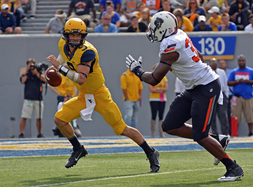 Photo - West Virginia quarterback Clint Trickett (9) avoids the pass rush in the third quarter of an NCAA college football game against Oklahoma State in Morgantown, W.Va., on Saturday, Sept. 28, 2013. (AP Photo/Tyler Evert) ORG XMIT: WVTE304