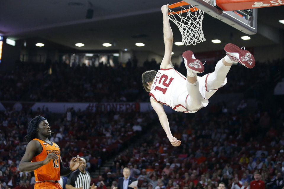 Photo - Oklahoma's Austin Reaves (12) hangs on the rim after a dunk as Oklahoma State's Isaac Likekele (13) waits for the ball during a Bedlam college basketball game between the University Oklahoma Sooners (OU) and the Oklahoma State Cowboys (OSU) at the Lloyd Noble Center in Norman, Okla., Saturday, Feb. 1, 2020. Oklahoma won 82-69. [Bryan Terry/The Oklahoman]