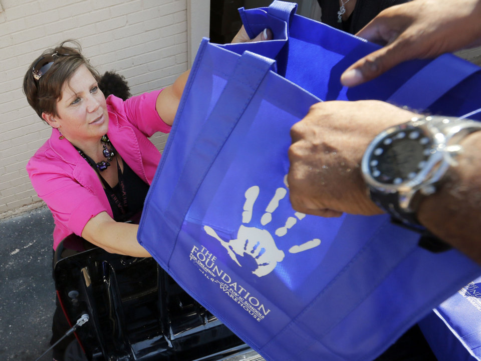 Christine Cooper, a fifth-grade teacher at Cesar Chavez Elementary, hands a bag of school supplies to volunteer Tagzmin Cudjoe as Cooper picks up supplies for her school at the Foundation for Oklahoma City Public Schools. The foundation, through its Teachers Warehouse program, recently reached the $1 million mark for giving away school supplies. Photo by Nate Billings, The Oklahoman <strong>NATE BILLINGS - THE OKLAHOMAN</strong>