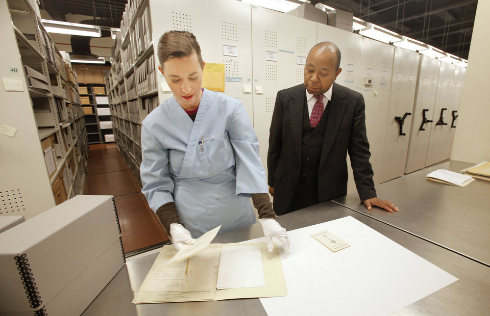 Historian Currie Ballard, right, looks on as Jennifer Day, manuscript archivist at the Oklahoma History Center, places items on a table from the black history collection he donated to the Oklahoma History Center. <strong>PAUL B. SOUTHERLAND - The Oklahoman</strong>