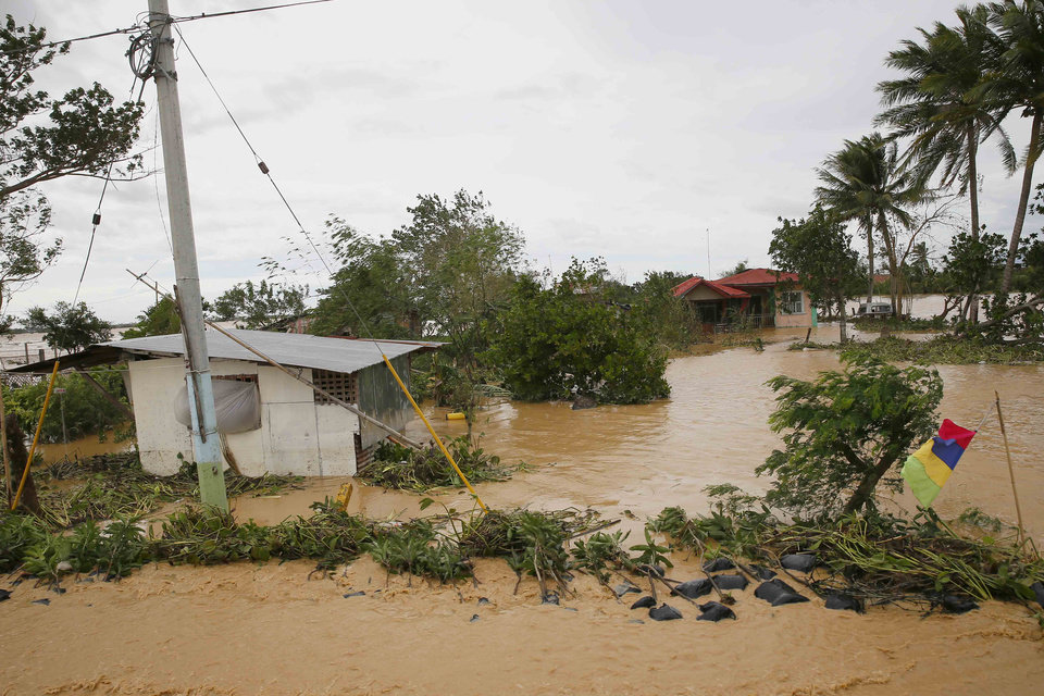 Photo - Houses continue to be inundated by flooding caused by Typhoon Koppu at Zaragosa township in Nueva Ecija province, north of Manila, Philippines Monday, Oct. 19, 2015. The slow-moving typhoon blew ashore with fierce wind in the northeastern Philippines early Sunday, toppling trees and knocking out power and communications and forcing the evacuation of thousands of villagers.(AP Photo/Bullit Marquez)