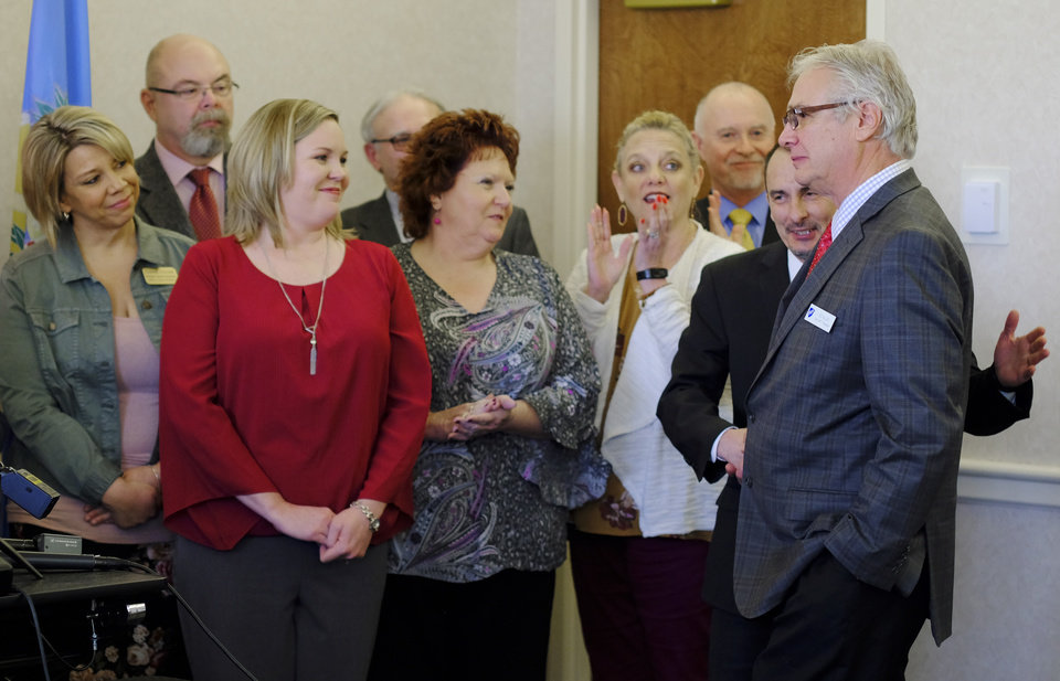 Photo -  Ed Allen, president of the Oklahoma City American Federation of Teachers, is welcomed to the group during a news conference at the Oklahoma Education Association. [Photo by Doug Hoke, The Oklahoman]