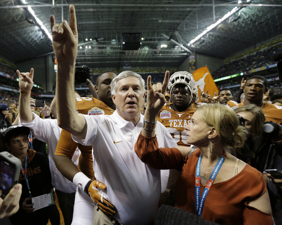 Photo - Texas coach Mack Brown, left, and his wife Sally, right, sing the school song after  the Valero Alamo Bowl NCAA college football game against Oregon, Monday,  Dec. 30, 2013, in San Antonio. Oregon won 30-7. (AP Photo/Eric Gay)