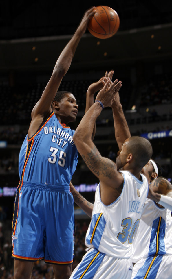 Photo - Oklahoma City Thunder forward Kevin Durant, left, takes to the air to pass the ball over Denver Nuggets guard Dahntay Jones, front right, and forward Renaldo Balkman in the first quarter of an NBA basketball game in Denver on Wednesday, April 8, 2009. (AP Photo/David Zalubowski) ORG XMIT: CODZ105