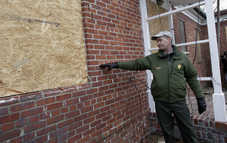 Photo - David Luchsinger, superintendent of Statue of Liberty National Monument, and last resident of Liberty Island, shows the high water line at the back of his Superstorm Sandy-damaged home, on Liberty Island in New York, Friday, Nov. 30, 2012. Tourists in New York will miss out for a while on one of the hallmarks of a visit to New York _ seeing the Statue of Liberty up close. Though the statue itself survived Superstorm Sandy intact, damage to buildings and Liberty Island's power and heating systems means the island will remain closed for now, and authorities don't have an estimate on when it will reopen. (AP Photo/Richard Drew)