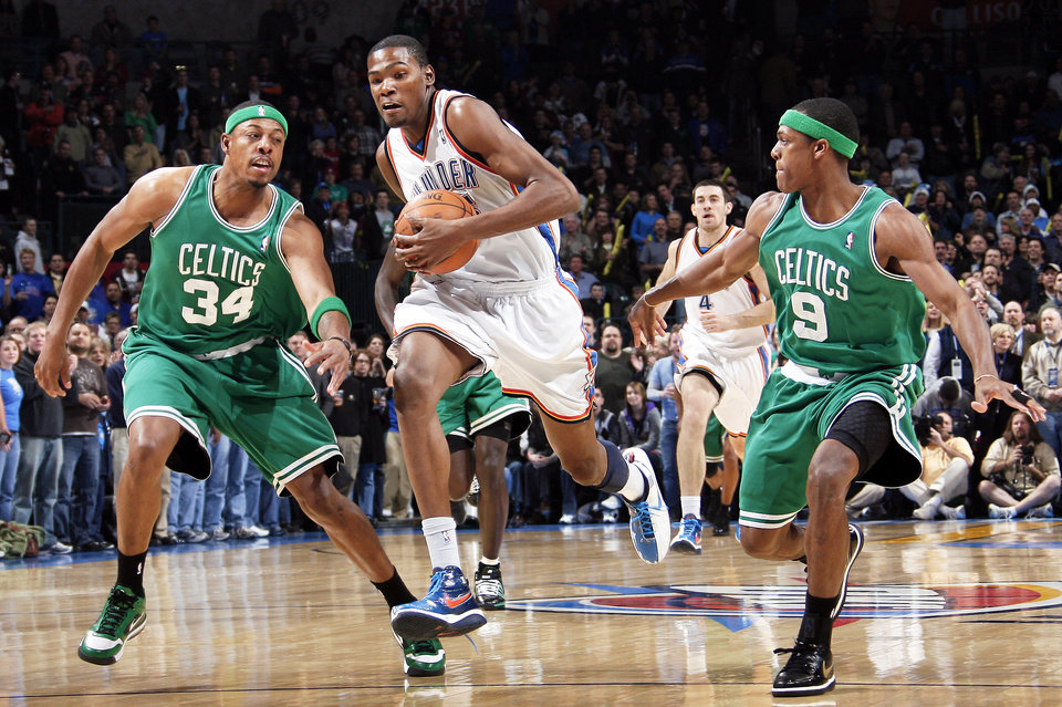 Photo - Oklahoma City's Kevin Durant, center, tries to get past Paul Pierce, left, and Rajon Rondo of Boston in the first half.  Photo by Nate Billings, The Oklahoman
