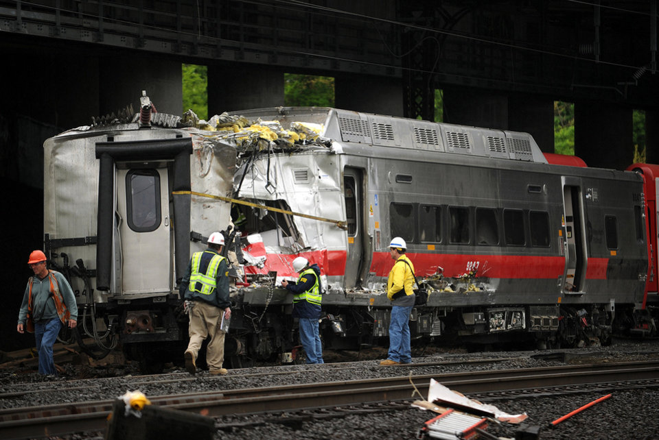 Photo - Metro-North employees work at the site of Friday's train derailment in Bridgeport. Conn. on Sunday, May 19, 2013. Crews will spend days rebuilding 2,000 feet of track, overhead wires and signals following the collision between two trains Friday evening that injured 72 people, Metro-North President Howard Permut said Sunday. (AP Photo/The Connecticut Post,Brian A. Pounds ) MANDATORY CREDIT