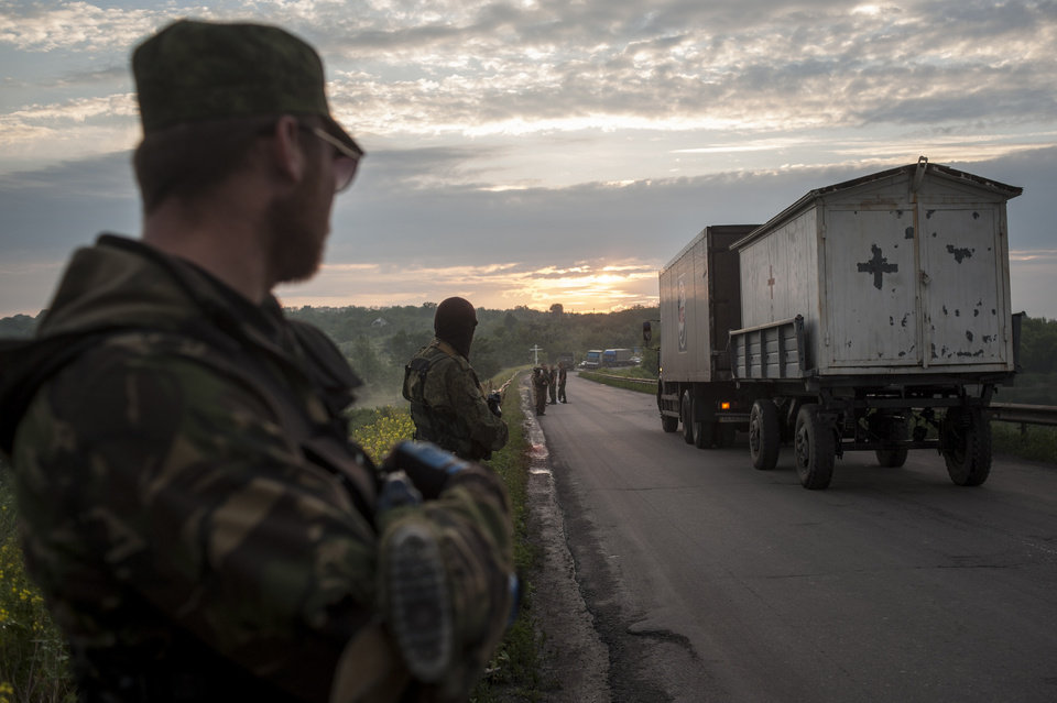 Photo - Pro-Russian fighters handover the bodies of Ukrainian troops who died in a plane shot down near Luhansk, at a check point in the village of Karlivka near Donetsk, eastern Ukraine, Wednesday, June 18, 2014. The two sides managed to arrange a brief truce Wednesday evening in the eastern town of Karlivka to allow pro-Russian forces to hand over the bodies of 49 Ukrainian troops who died when the separatists shot down a transport plane bound for the airport in Luhansk last weekend. (AP Photo/Evgeniy Maloletka)