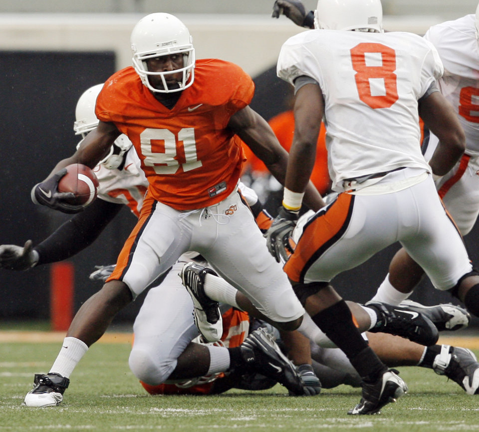 Photo - OSU's Justin Blackmon (81) moves around Daytawion Lowe (8) on his way to a touchdown during the Oklahoma State Orange and White spring football game at Boone Pickens Stadium in Stillwater, Okla., Saturday, April 17, 2010. Photo by Nate Billings, The Oklahoman