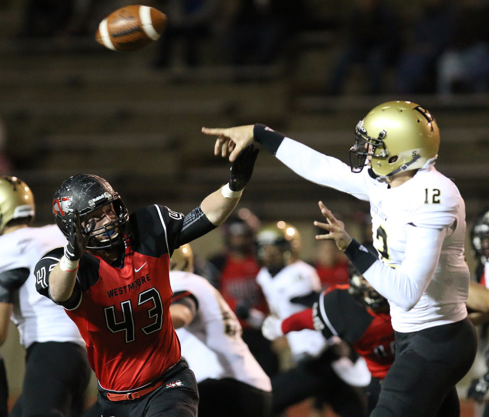 WM #43 Jacob Tilley pressures BA #12 QB Coleman Key during the high school football game between Broken Arrow and Westmoore at Moore stadium Friday , November 8, 2013. Photo by Doug Hoke, The Oklahoman