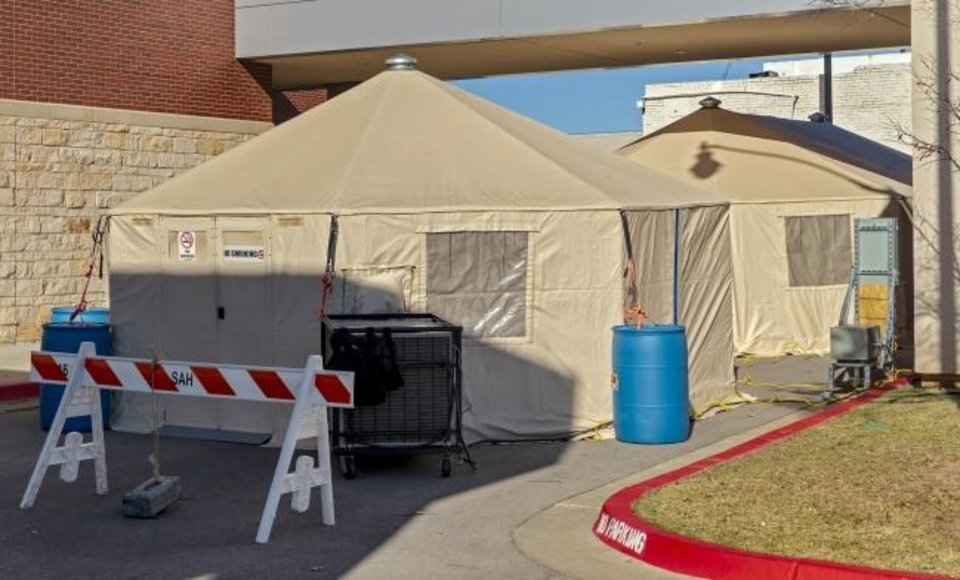 Photo -  Overflow tents have been set up outside of SSM Health St. Anthony to deal with the COVID-19 outbreak in Oklahoma City.  [Chris Landsberger/The Oklahoman]