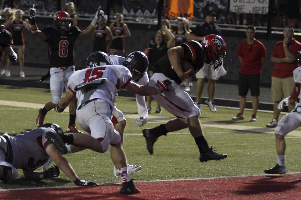 Photo - Mustang quarterback Frankie Edwards jumps into the end zone to give the Broncos a 7-0 lead with 21 seconds left in the second quarter during the Mustang - Yukon High School football  season opener Friday night at Bronco Stadium in Mustang. Photo by Hugh Scott, for the Oklahoman