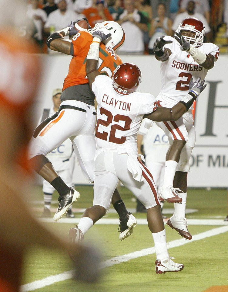 Photo - Miami's Dedrick Epps catches a touchdown pass between OU's Keenan Clayton, left, and Brian Jackson during the college football game between the University of Oklahoma (OU) Sooners and the University of Miami (UM) Hurricanes at Land Shark Stadium in Miami Gardens, Florida, Saturday, October 3, 2009. Photo by Bryan Terry, The Oklahoman ORG XMIT: KOD