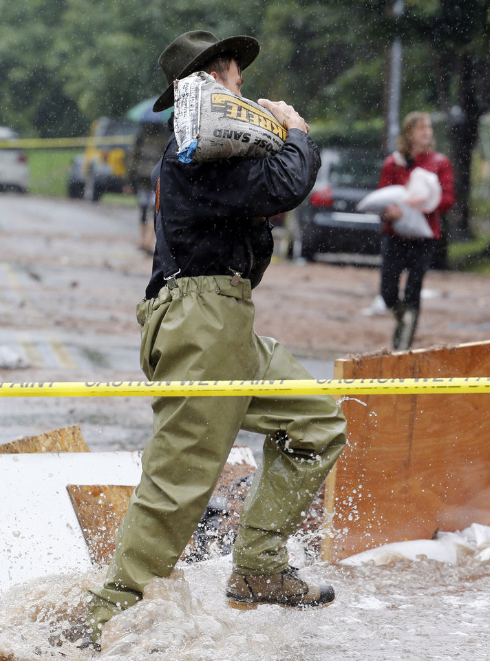 Photo - A man carries a sandbag through flood waters as residence of an apartment house work to divert flood water from their building in Boulder, Colo., on Thursday, Sept. 12, 2013. Flash flooding in Colorado has cut off access to towns, closed the University of Colorado in Boulder and left at least three people dead. (AP Photo/Ed Andrieski)
