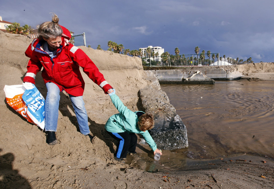 Photo - Meredith McCarthy and her son Jasper Ward, 7, retrieve a plastic bottle as volunteers with Heal The Bay's storm response team remove snack-food packaging, plastic drink containers, single-use bags and other debris washed into the ocean from the Pico-Kenter outfall, a storm drain that serves a large part of the Westside of Los Angeles, at Santa Monica Beach, Friday, Feb. 28, 2014. Heavy rains will flush accumulated trash into the ocean, where it becomes a health hazard to humans and sea life. (AP Photo/Reed Saxon)
