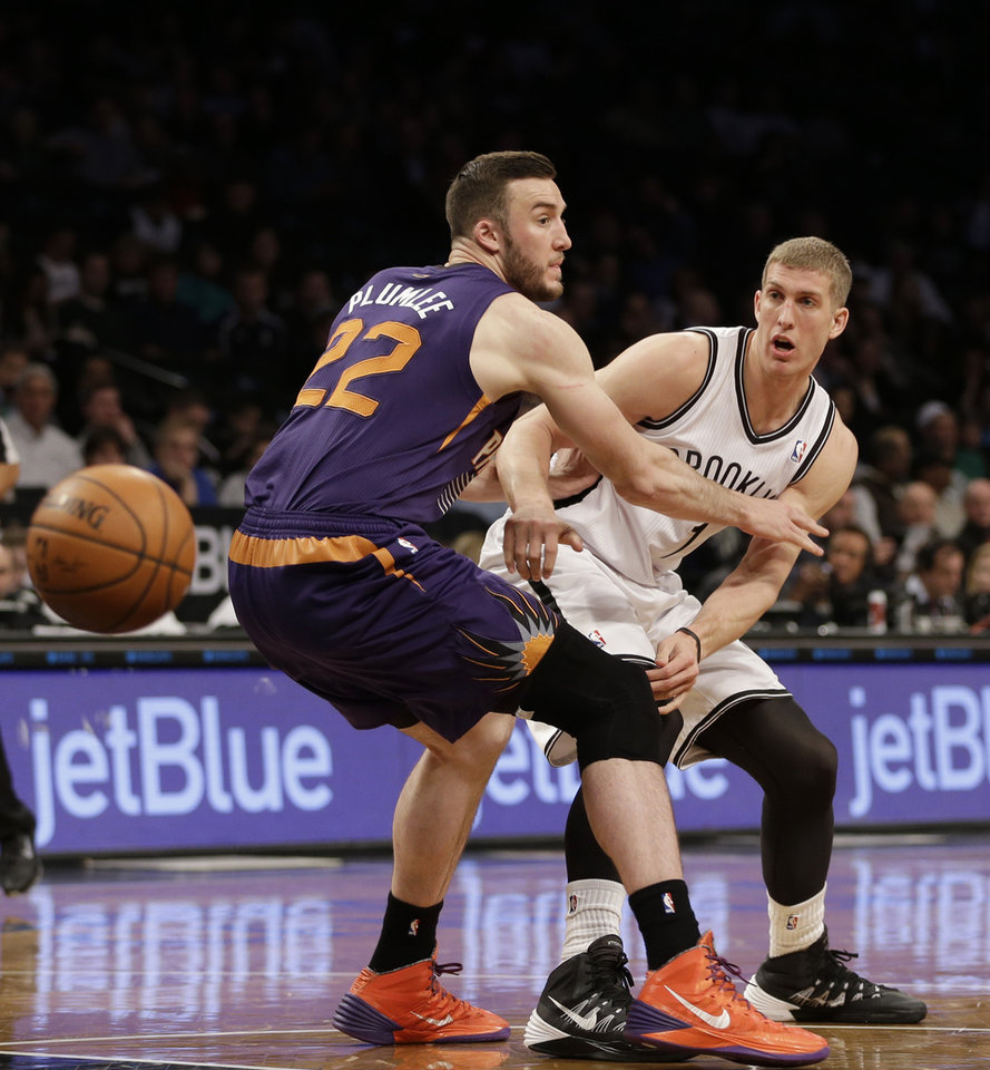 Photo - Brooklyn Nets's Mason Plumlee, right, passes around Phoenix Suns' Miles Plumlee during the first half of the NBA basketball game at the Barclays Center Monday, March 17, 2014 in New York. (AP Photo/Seth Wenig)