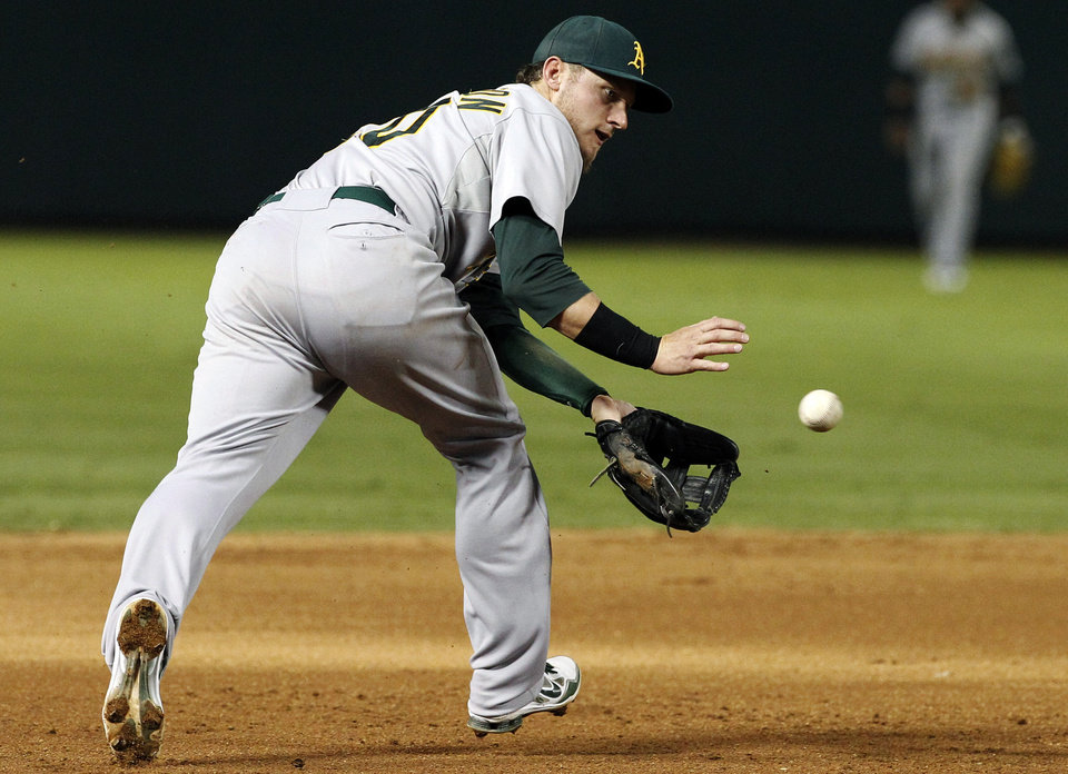Photo -   Oakland Athletics third baseman Josh Donaldson chases down a ground out by Texas Rangers' Ian Kinsler in the fifth inning of a baseball game, Tuesday, Sept. 25, 2012, in Arlington, Texas. (AP Photo/Tony Gutierrez)