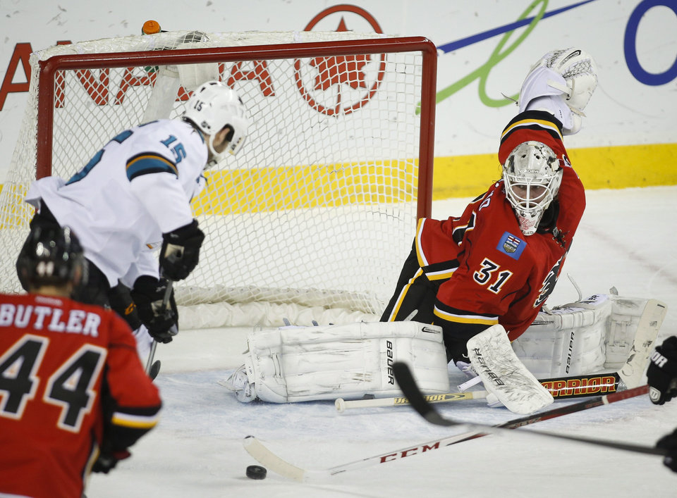 Photo - San Jose Sharks' James Sheppard, left, scores on Calgary Flames' goalie Karri Ramo, from Finland, during first period NHL hockey action in Calgary, Monday, March 24, 2014. (AP Photo/The Canadian Press, Jeff McIntosh)