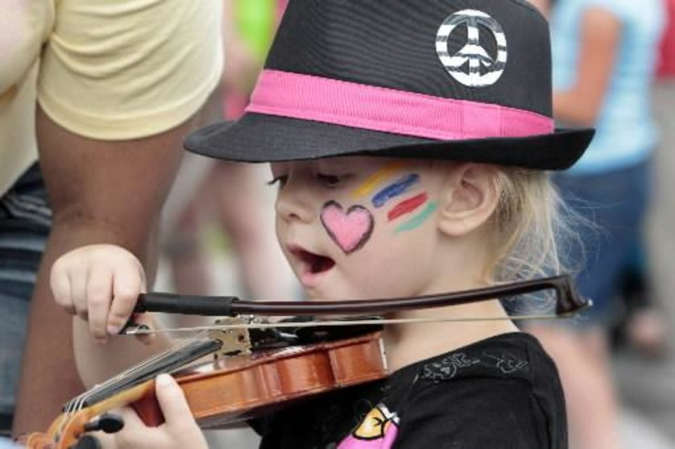 Skylar Allen, 3, gets to try out a violin at the children's area during the Norman Music Festival on Saturday, April 28, 2012, in Norman, Okla. Photo by Steve Sisney, The  Oklahoman Archives
