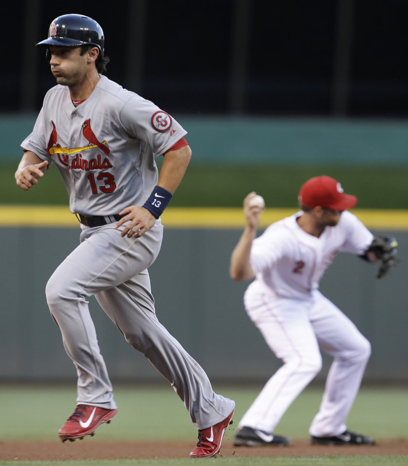Photo - St. Louis Cardinals' Matt Carpenter (13) runs to third as Cincinnati Reds shortstop Zack Cozart throws to second base to start a double play after fielding a ground ball hit by Allen Craig in the first inning of a baseball game, Tuesday, Sept. 3, 2013, in Cincinnati. (AP Photo/Al Behrman)