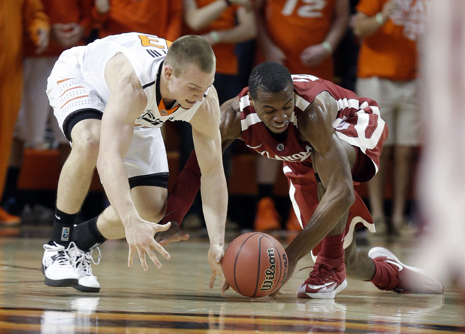 Photo - Oklahoma State's Phil Forte, III (13) and Oklahoma's Buddy Hield (24) fight for a loose ball during the men's Bedlam college game between Oklahoma and Oklahoma State at Gallagher-Iba Arena in Stillwater, Okla., Saturday, Feb. 15, 2014. Photo by Sarah Phipps, The Oklahoman