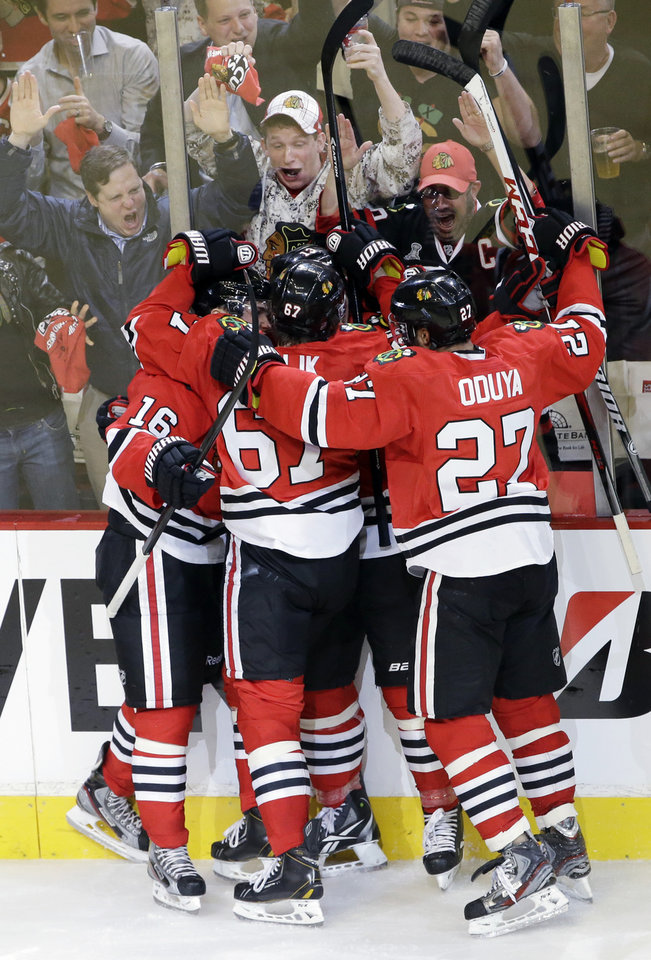 Photo - Chicago Blackhawks' Marcus Kruger (16), left, celebrates with teammates after scoring a goal during the third period of Game 1 of an NHL hockey playoffs Western Conference semifinal against the Detroit Red Wings in Chicago, Wednesday, May 15, 2013. (AP Photo/Nam Y. Huh)