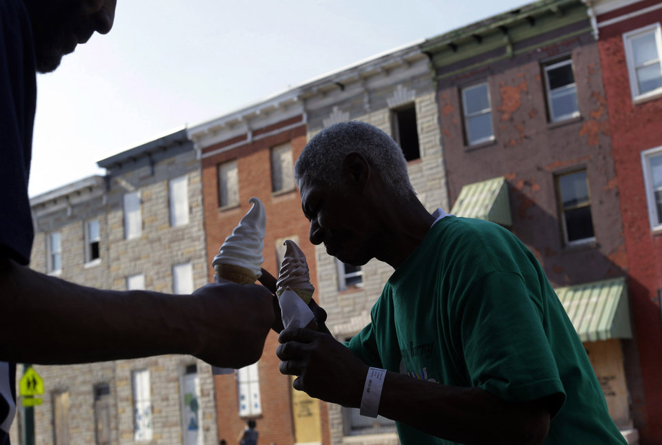 Photo - In this Tuesday, April 9, 2013 photo, two homeless men who gave their names as Earl, right, and Angelo, eat ice cream cones across the street from a block of vacant row houses in Baltimore. A biennial census of Baltimore's homeless population that is mandated by the U.S. Department of Housing and Urban Development counted more than 4,000 homeless people in 2011. Some choose to seek shelter in the city's estimated 16,000 buildings that are vacant or abandoned. (AP Photo/Patrick Semansky)