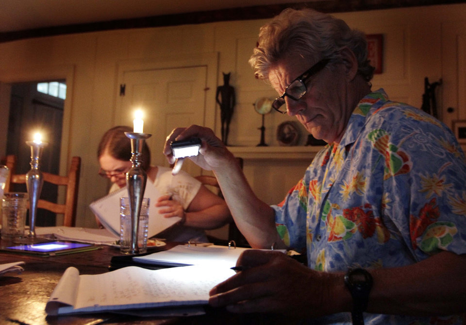 Photo -   In this photo taken Sunday Aug. 21, 2011 Academy Award winner Ernest Thompson use candles and light from his cell phone to go over the script with his cast and crew after loosing power from a powerful thunderstorm in New Hampton, N.H. Thirty years after the academy award winning movie,