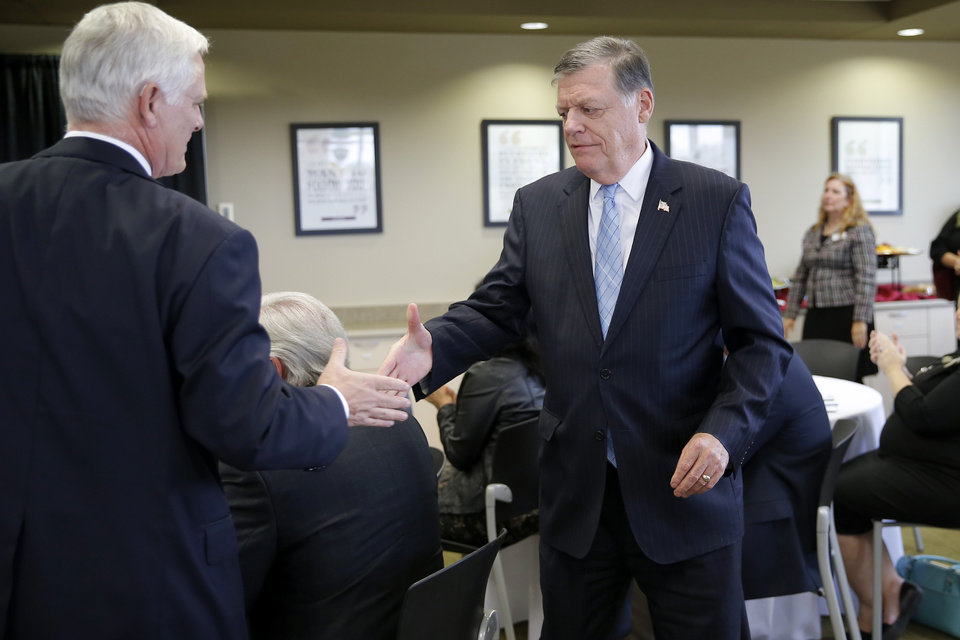 Photo - Jim Gallogly, left, University of Oklahoma president, shales hands with U.S. Rep. Tom Cole during an event at the University of Oklahoma's K20 Center for Educational and Community Renewal on Wed., Nov. 7, 2018. The center received three Gaining Early Awareness and Readiness for Undergraduate Programs grants sponsored by the U.S. Department of Education. Photo by Bryan Terry, The Oklahoman